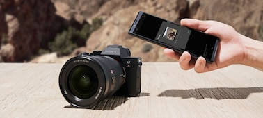 Image of the camera and a hand holding a device