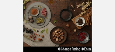 "Image of food on a table as seen through the monitor, with a ""Change Rating"" control visible"