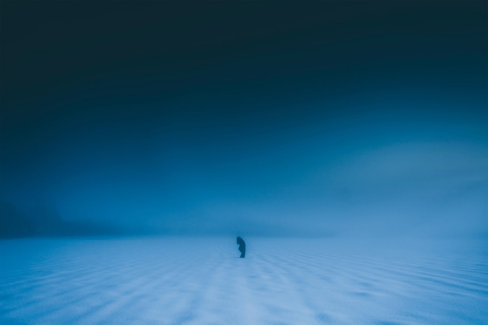 person in snowy field at night
