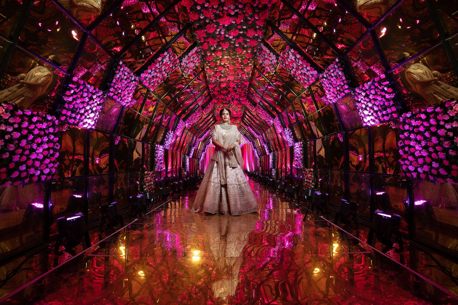 woman standing in middle of glass corridor filled with flowers alpha 9