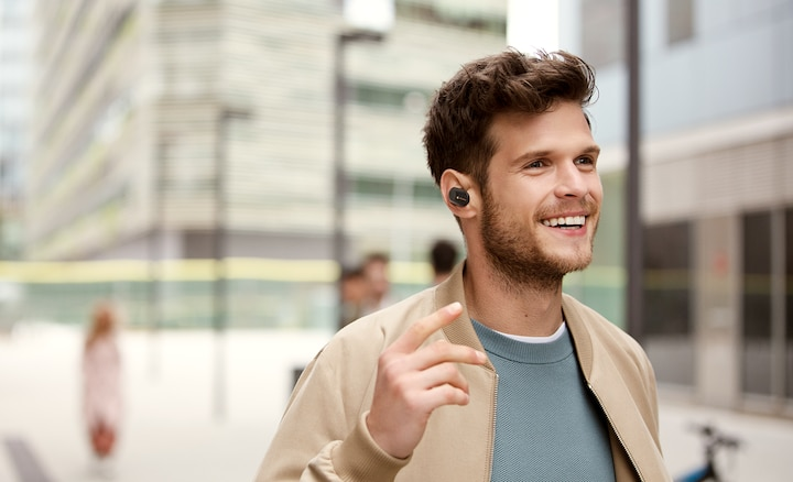 Lifestyle image of man using WF-1000XM3 earbuds for hands-free calling.