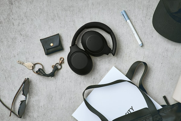 Lifestyle shot showing foldable design of WH-XB900N headphones.