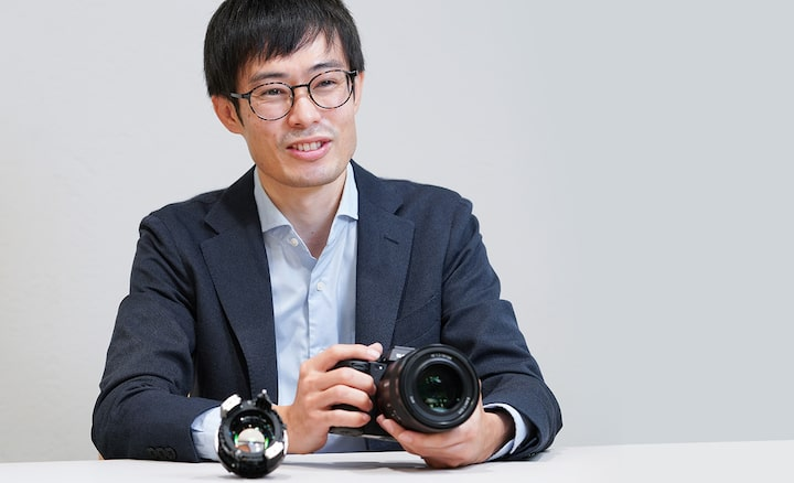 The Mechanical Design Lead holds the FE 50mm F1.2 while delivering an explanation
