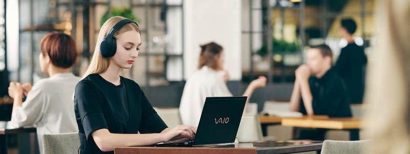 Lifestyle image of woman using laptop, wearing WH-H910N headphones