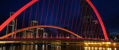 Nighttime image of a cityscape, with an illuminated red-coloured bridge in the foreground